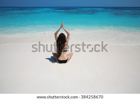 Young woman practicing yoga on the exotic beach with blue water and white sand. Relax. Meditation, peace. Balance. Bliss freedom concept.   - stock photo