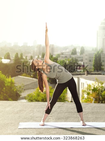 Young woman practicing yoga on the mat on the roof  and doing yoga exercises