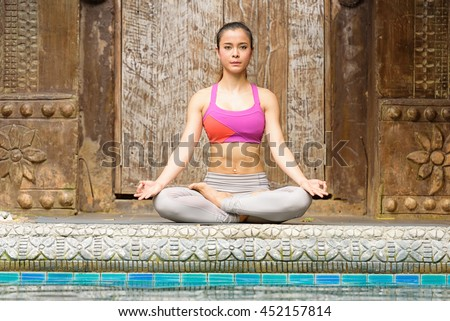 Young woman practicing yoga on the pool. - stock photo