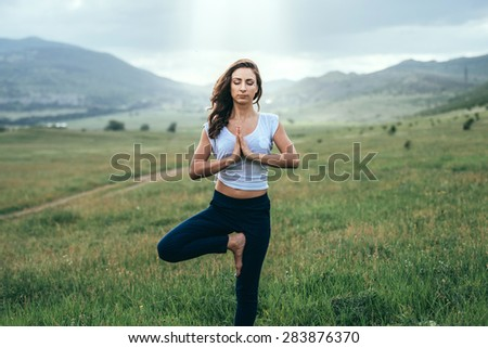 Young woman practicing yoga outdoor in the nature - stock photo