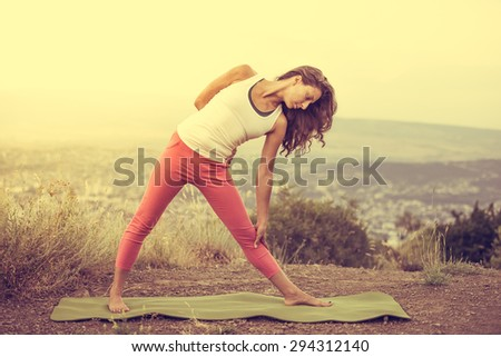 Young woman practicing yoga outdoor in the nature with city on background. Toned image - stock photo