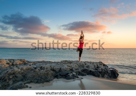 Young woman practicing yoga. Paradise beach and colorful sunrise. - stock photo