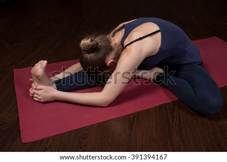 Young woman practicing yoga. The girl took a pose of yoga. Lies stretching out one leg, bending body to her