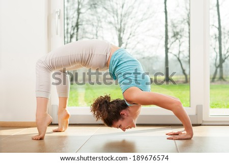 Young woman practicing yoga - Urdhva Dhanurasana / Upward bow pose indoor in fron of the window - stock photo