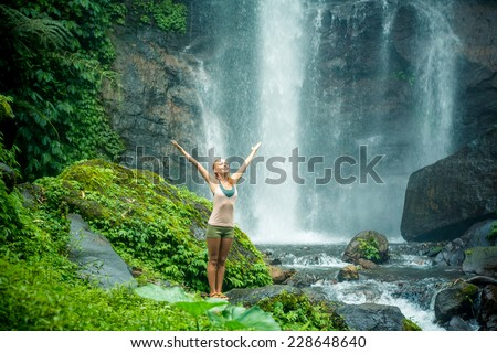 Young woman practicing yoga with waterfall in the background - stock photo