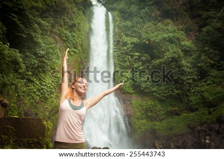 Young woman practicing yoga with waterfall in the background