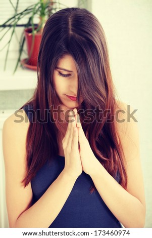 Young woman praying at home - stock photo