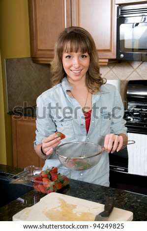 Young woman prepares strawberries