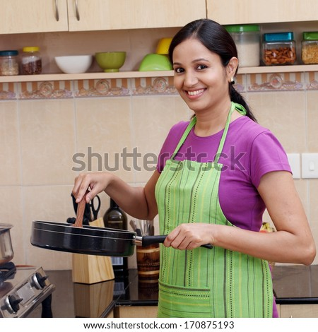 Young woman preparing a dish in her kitchen