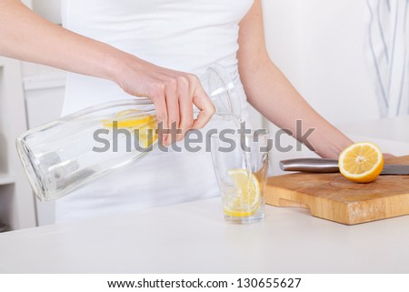 young woman preparing and drinking lemonade in her modern kitchen