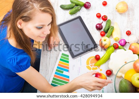 Young woman preparing breakfast while getting online information about nutrition.  - stock photo