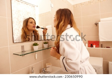 Young woman preparing makeup in the morning. - stock photo