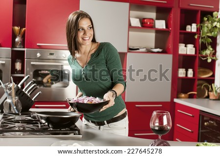 Young woman preparing meal in the kitchen - stock photo