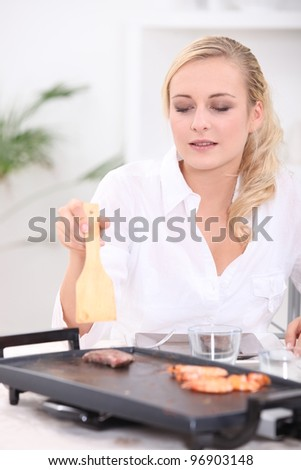 Young woman preparing meal on a griddle