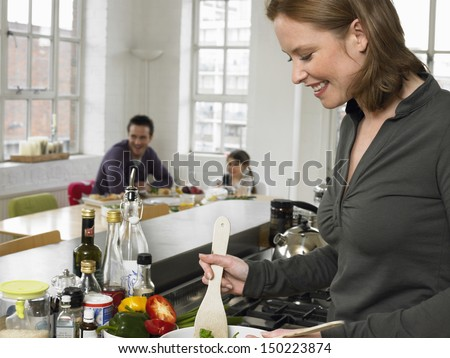 Young woman preparing salad with family sitting in background at home - stock photo