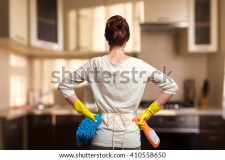 Young woman preparing to clean the kitchen. Standing back - stock photo