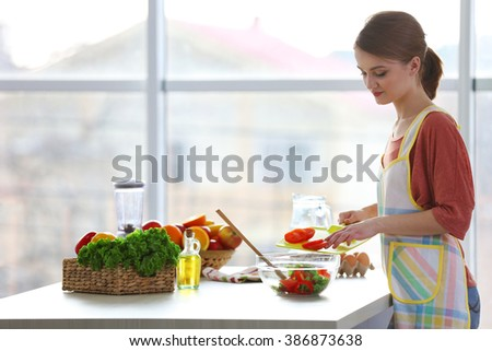 Young woman preparing vegetable salad in the kitchen - stock photo