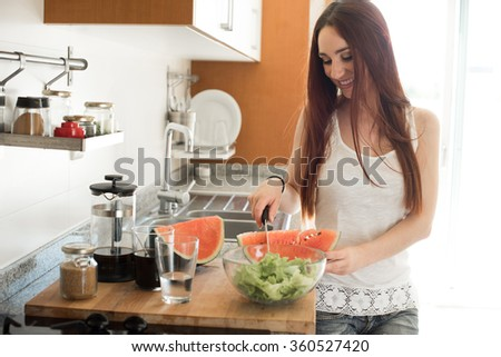 Young woman preparing watermelon in the kitchen