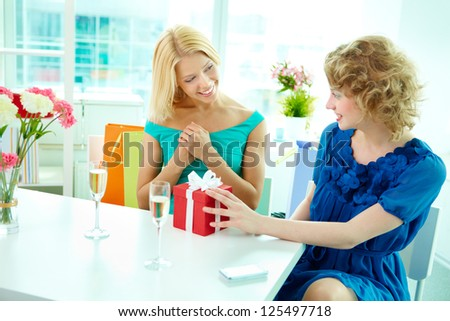 Young woman presenting a gift to her girlfriend in cafe - stock photo