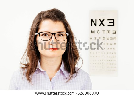 Young woman presenting a pair of glasses with eye chart behind - isolated on white.