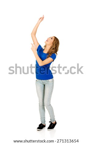Young woman presenting a product with arms raised. - stock photo