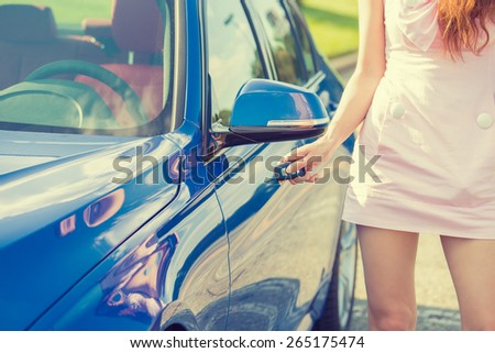 Young woman presses unlock button on car remote control unlocks door alarm systems. Vehicle convenience safety security system - stock photo