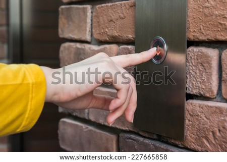 Young woman pressing elevator button - stock photo