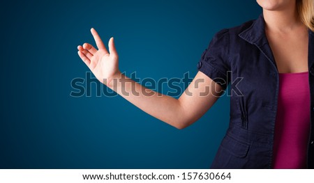 Young woman pressing imaginary button - stock photo