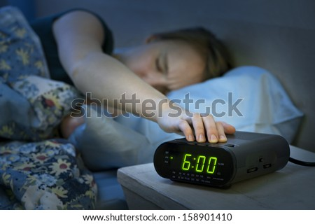Young woman pressing snooze button on early morning digital alarm clock radio - stock photo