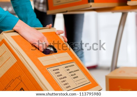 Young woman - presumably friends - with moving box in her house moving in or out of a apartment, focus on moving box - stock photo