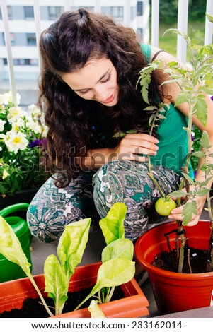 Young woman proud of her small kitchen garden in pots on the balcony - stock photo