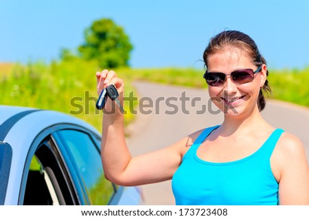 young woman proudly displays the keys to her new car - stock photo