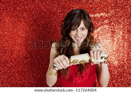Young woman pulling a Christmas cracker while standing in front of a red glitter background and wearing a red party dress.