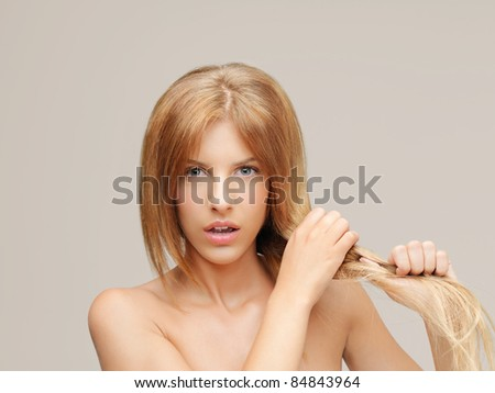 young woman pulling damaged hair both hands - stock photo