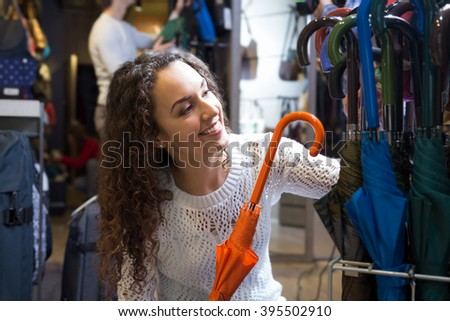Young woman purchasing new automatic umbrella in haberdashery shop