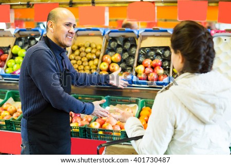 Young woman purchasing seasonal fruits in grocery from charming  seller