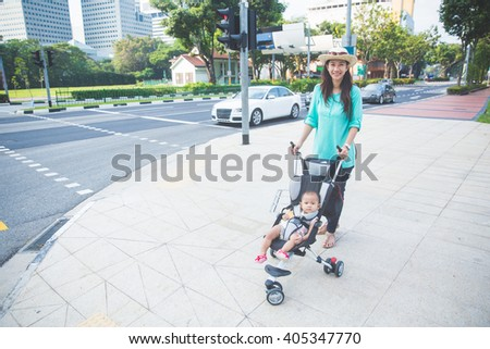 Young woman pushing her baby in stroller on the street sidewalk - stock photo