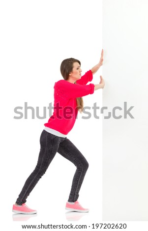 Young woman pushing the wall. Full length studio shot isolated on white. - stock photo