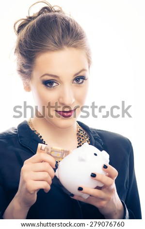 Young woman put 50 euro banknote in a piggy bank, isolated on white - stock photo