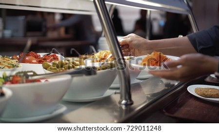 Young woman puts food on a plate on a food court