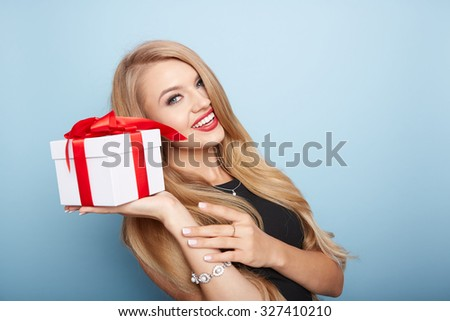 Young woman puts her ear to the present wrapped in white paper, isolated on white.