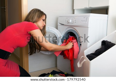 Young woman putting a cloth into washing machine  - stock photo