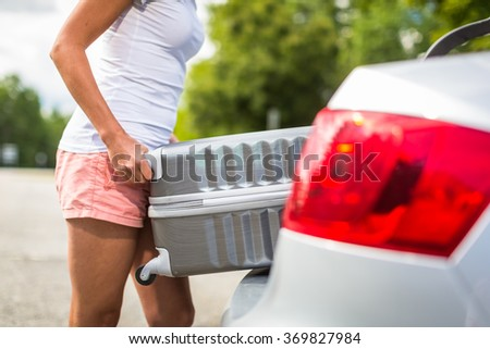 Young woman putting a have suitcase into her car's trunk - stock photo