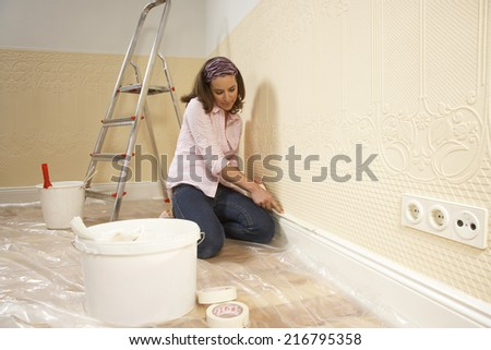 Young woman putting adhesive tape on a wall - stock photo