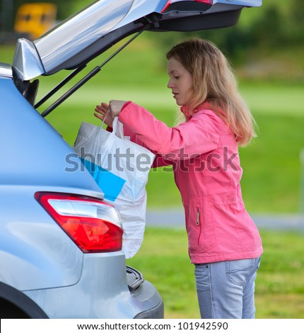 Young woman putting bag in car after shopping. - stock photo