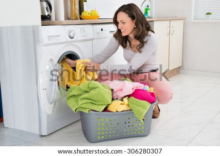 Young Woman Putting Clothes Into Washing Machine At Home
