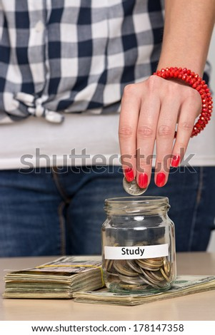 Young woman putting coin into a jar. She is saving money for better education. - stock photo
