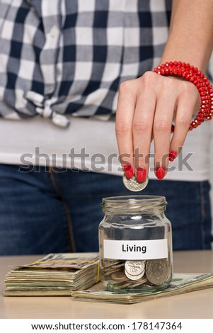 Young woman putting coin into a jar. She is saving money for the everyday life. - stock photo