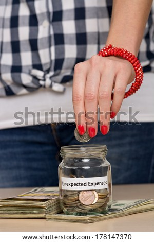 Young woman putting coin into a jar. She is saving money for unexpected expenses. - stock photo