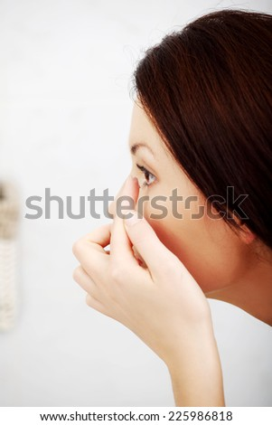 Young woman putting contact lens in her eye - stock photo